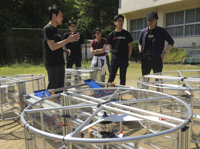 Cartivator members prepare for a test flight of their flying car model on a former school ground in Toyota, central Japan, Saturday, June 3, 2017. Cartivator Resource Management, in which Toyota invested 42.5 million yen ($386,000), showed to reporters Saturday a test flight of a concoction of aluminum framing and propellers. It took off several times, hovering as high as eye level for a few seconds, before falling to the ground. (AP Photo/Koji Ueda)